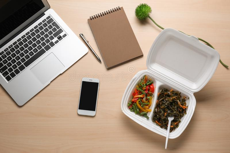 Flat lay composition with smartphone, laptop and takeout meal on wooden background. Food delivery royalty free stock photography