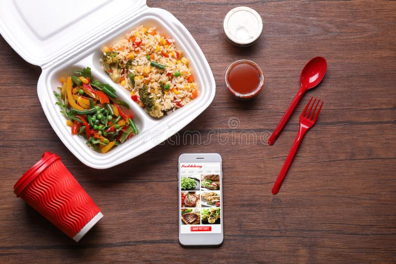 Flat lay composition with smartphone and takeout meal on wooden background. Food delivery royalty free stock photos