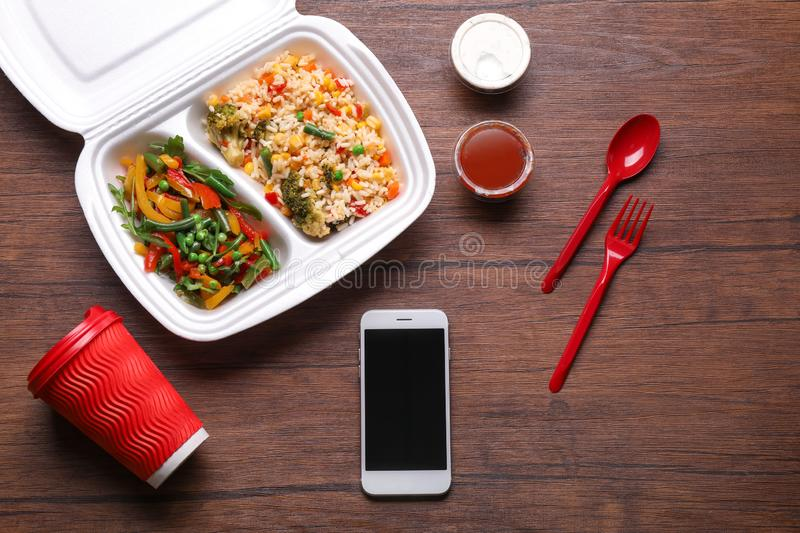 Flat lay composition with smartphone and takeout meal on wooden background. Food delivery stock images