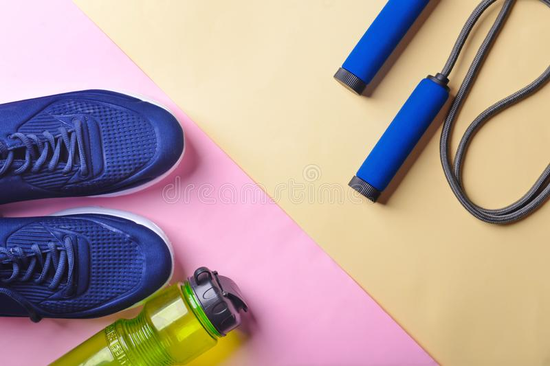 Flat lay composition with sneakers, bottle of water and jumping rope on color background. Gym workout royalty free stock image