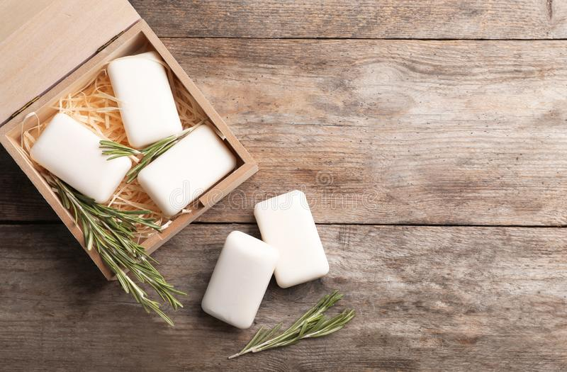 Flat lay composition with soap bars, rosemary and space for text. On wooden background stock image