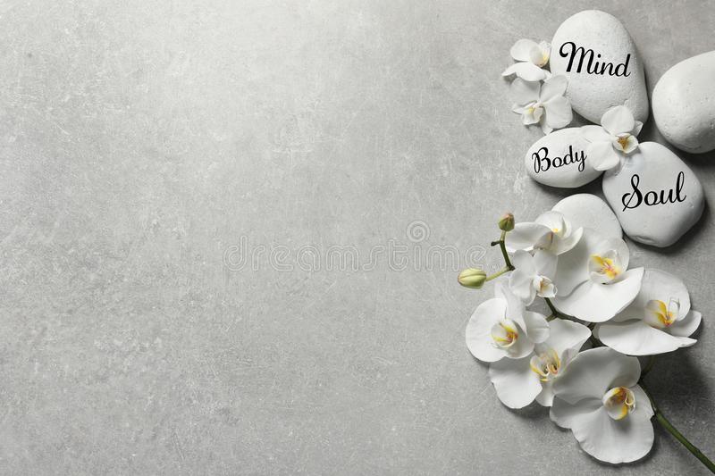 Flat lay composition with spa stones and orchid flowers on grey background. royalty free stock images