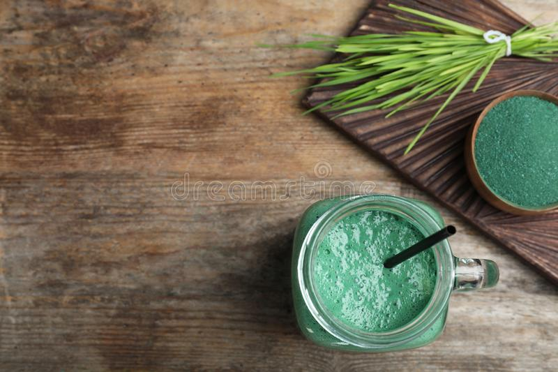 Flat lay composition with spirulina smoothie, powder and wheat grass on wooden background. Space for text royalty free stock images