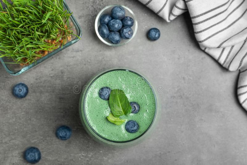 Flat lay composition with spirulina smoothie, wheat grass and blueberries. On grey background stock photography