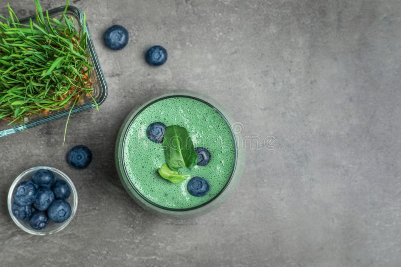 Flat lay composition with spirulina smoothie, wheat grass and blueberries on grey background. Space. For text royalty free stock image
