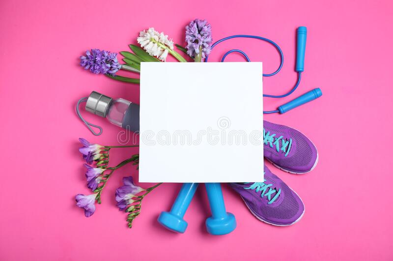 Flat lay composition with spring flowers, sports items and blank card on pink. Space for text. Flat lay composition with spring flowers, sports items and blank stock photos