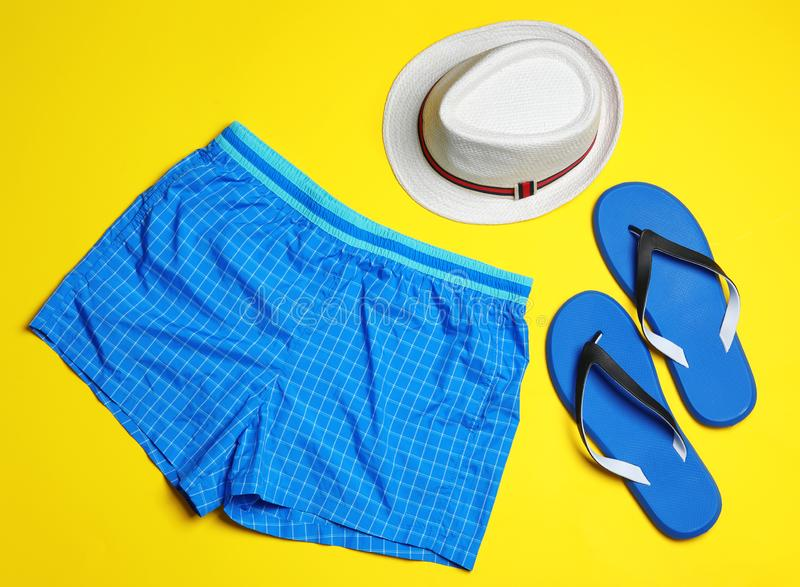 Flat lay composition with stylish male swim trunks. Beach objects. Flat lay composition with stylish male swim trunks on color background. Beach objects royalty free stock photos