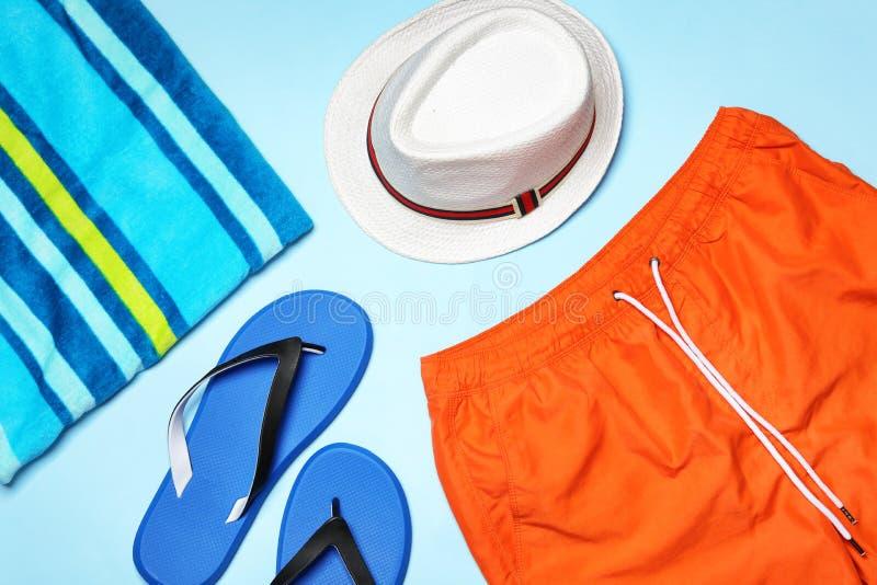 Flat lay composition with stylish male swim trunks. Beach objects. Flat lay composition with stylish male swim trunks on color background. Beach objects stock photo