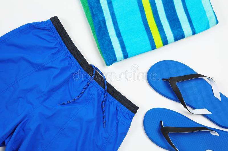 Flat lay composition with stylish male swim trunks on white background. Beach objects stock photography