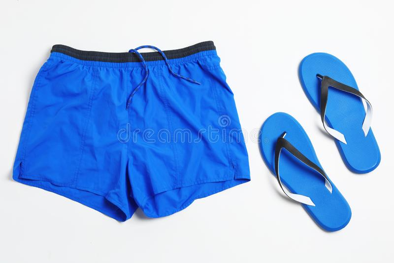 Flat lay composition with stylish male swim trunks on white background. Beach objects royalty free stock images