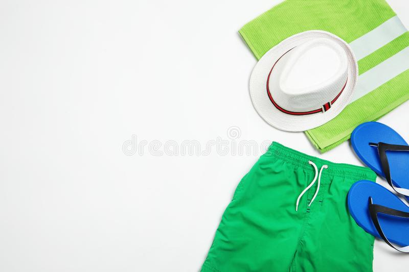 Flat lay composition with stylish male swim trunks on white background. Beach objects. Flat lay composition with stylish male swim trunks on white background royalty free stock photo