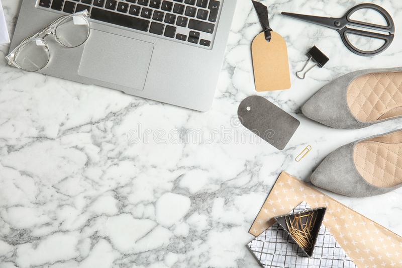 Flat lay composition with stylish shoes, laptop and space for text on marble background. stock photo