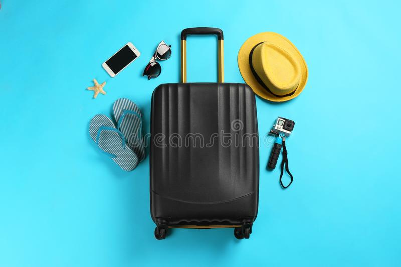 Flat lay composition with suitcase and traveler`s accessories. On color background stock image