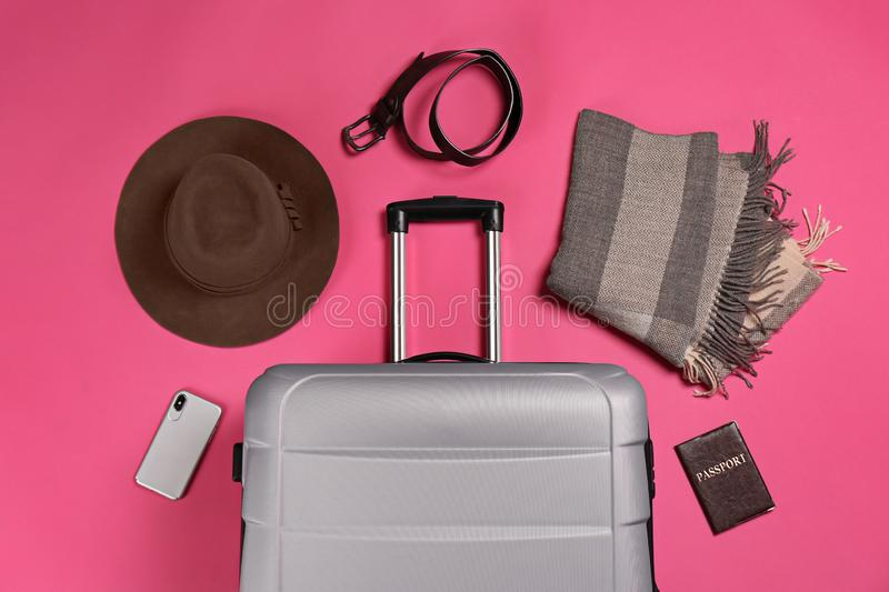Flat lay composition with suitcase and traveler`s accessories. On color background stock images