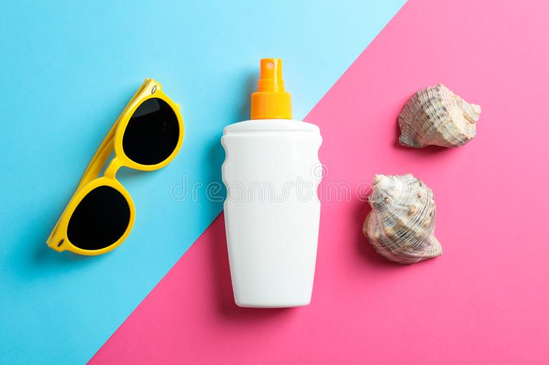 Flat lay composition with sunglasses, sunscreen pray and seashell on two tone background, top view, closeup. Summer vacation backdrop stock image