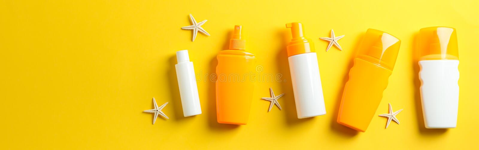 Flat lay composition with sunscreen sprays and starfishes on color background, space for text stock photo