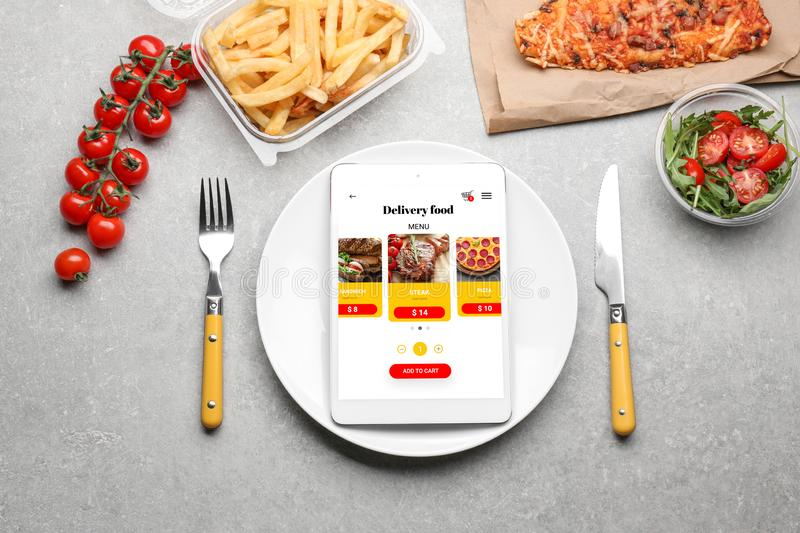 Flat lay composition with tablet computer and takeout meals on grey background. Food delivery stock image