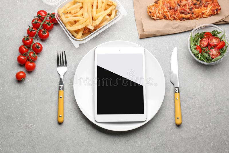 Flat lay composition with tablet computer and takeout meals on grey background. Food delivery royalty free stock images