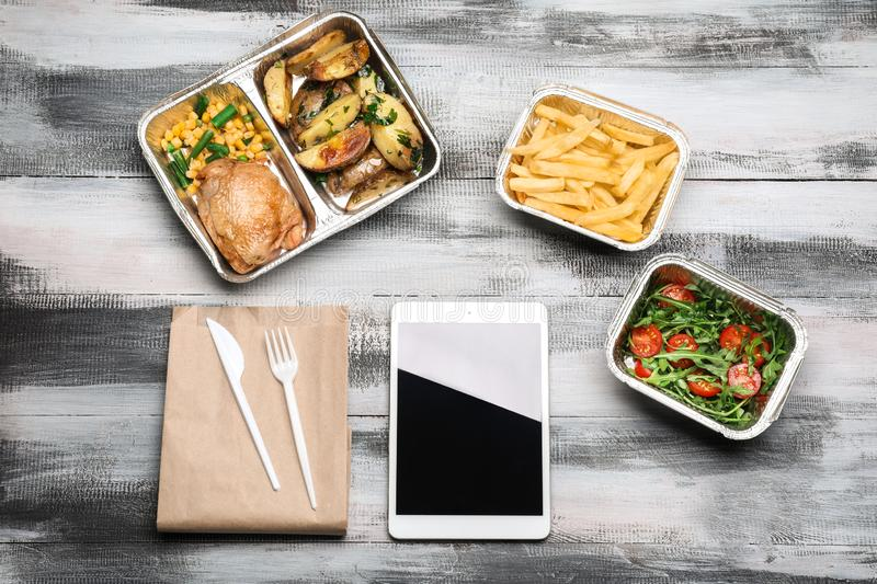 Flat lay composition with tablet computer and takeout meals on wooden background. Food delivery stock image
