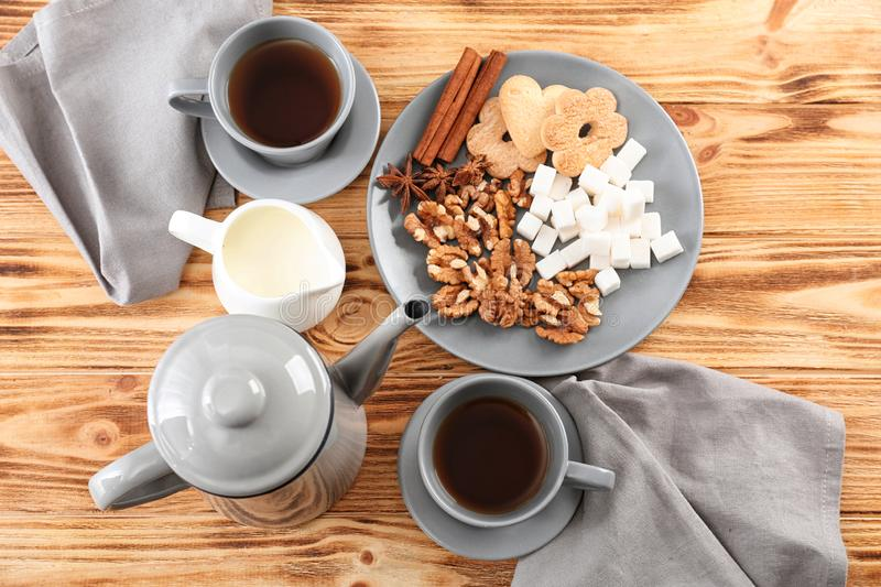 Flat lay composition with tea, milk and treats on table stock photo