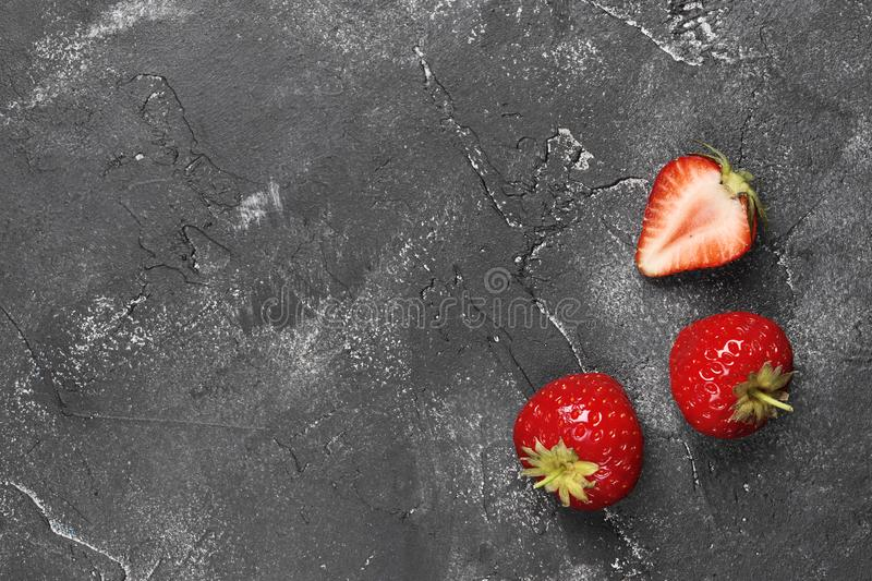 Flat lay composition of three ripe strawberries on a dark background stock image