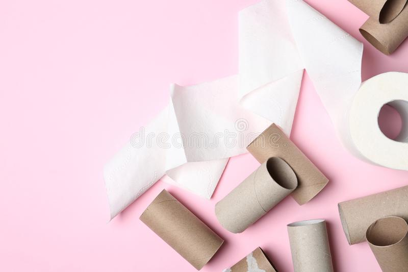 Flat lay composition with toilet paper and empty rolls on color background. Space for text stock photos