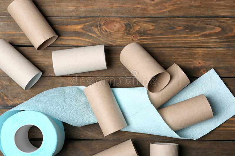 Flat lay composition with toilet paper and empty rolls. On wooden background stock photos