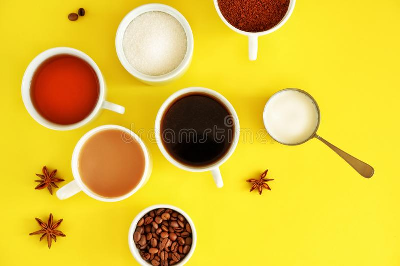 Flat lay composition of various cups of coffee, tea with sugar, cream and star anise on a bright yellow background. royalty free stock photography