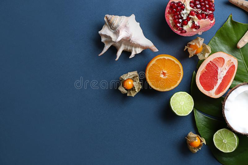 Flat lay composition with various delicious exotic fruits and tropical leaf on color background stock photography