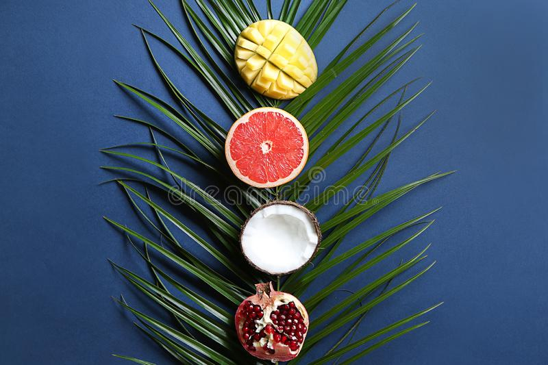 Flat lay composition with various delicious exotic fruits and tropical leaf on color background royalty free stock image