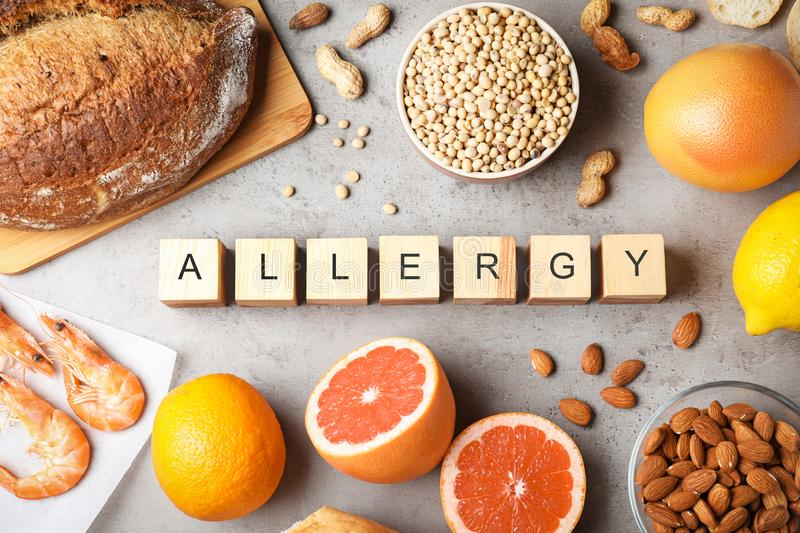Flat lay composition of various foods and wooden cubes with word Allergy on table royalty free stock photography