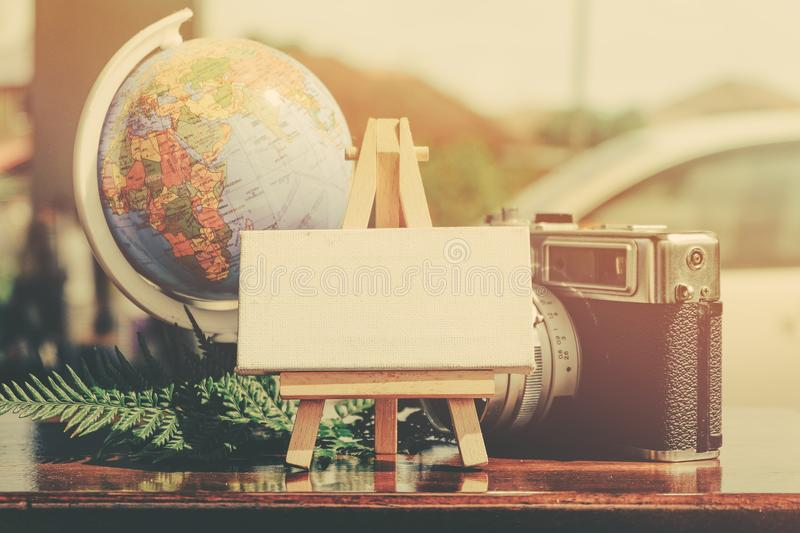 flat lay composition of vintage camera,compass, green plant and word block on wooden table royalty free stock image