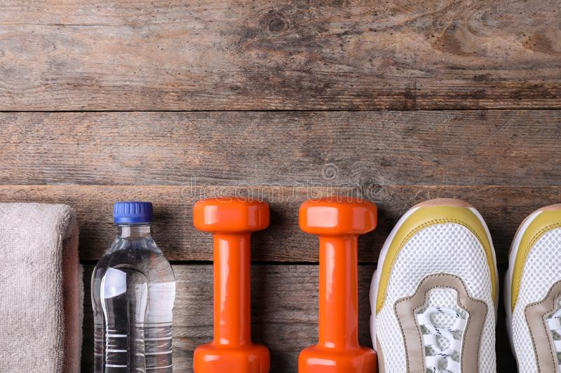 Flat lay composition with vinyl dumbbells, sneakers and space for text royalty free stock photography