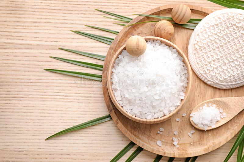 Flat lay composition with white sea salt on wooden background. Spa treatment. Flat lay composition with white sea salt on wooden background, space for text. Spa stock photography