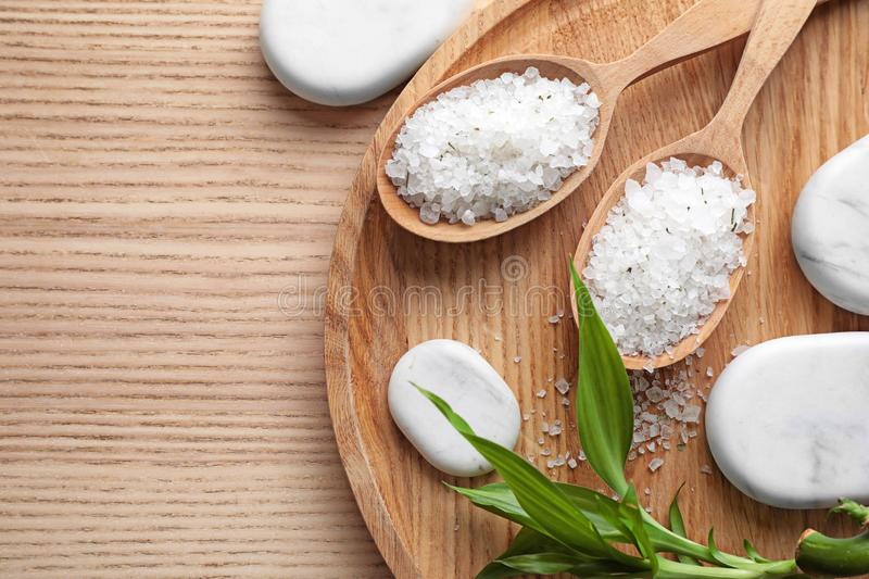 Flat lay composition with white sea salt on wooden background. Spa treatment. Flat lay composition with white sea salt on wooden background, space for text. Spa stock image