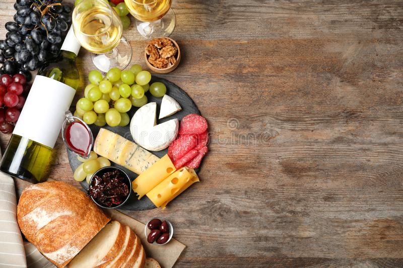 Flat lay composition with wine, snacks on wooden background royalty free stock photos