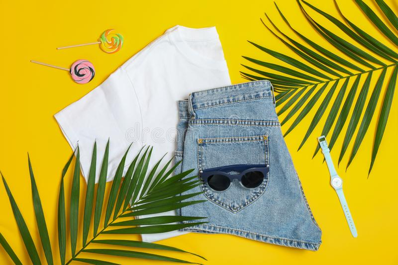 Flat lay composition with: women clothes and accessories, palm leaf and candy canes on yellow background royalty free stock image