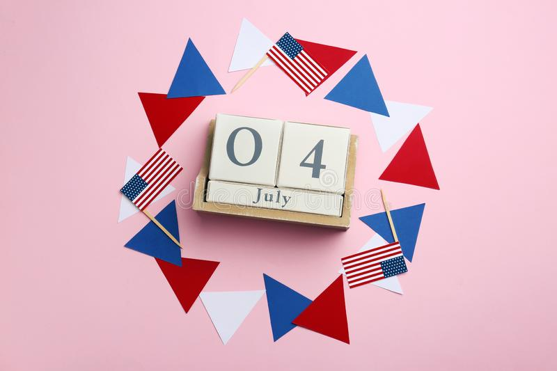 Flat lay composition with wooden calendar and USA flags. Happy Independence Day. Flat lay composition with wooden calendar and USA flags on color background royalty free stock image