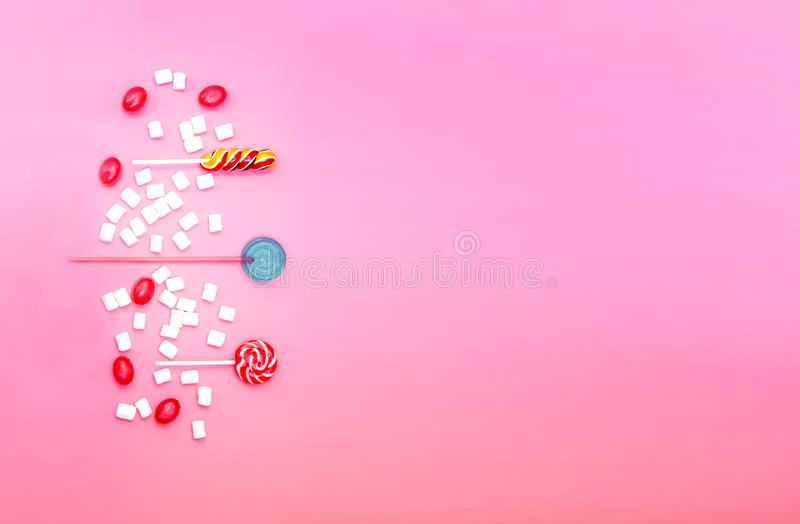 Flat lay composition with yummy lollipops and marshmallows and space for text on pink background stock image