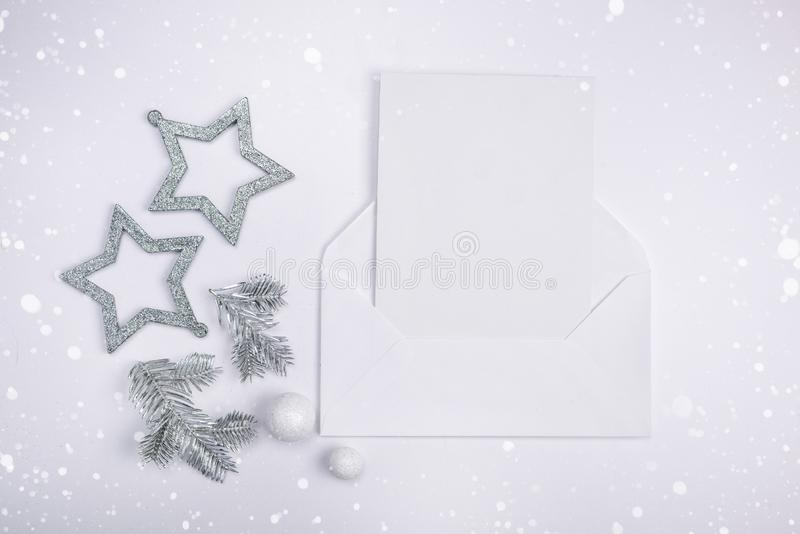 Flat lay compositions with Christmas decor silver stars, silver spruce branches and a letter greeting card copy space. Flat lay compositions with Christmas decor stock photo