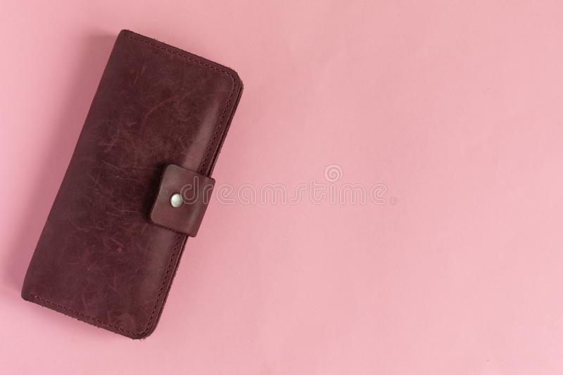 Female wine-colored wallet on pastel pink background royalty free stock photo