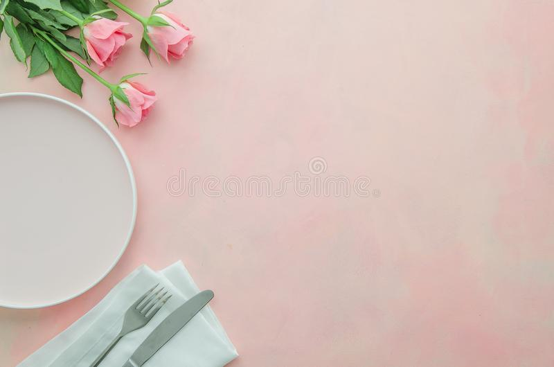Flat lay corner restaurant table for romantic dinner with pink rose flowers, dish and silverware knife, fork and napkins. Copy space for banner or menu stock photo