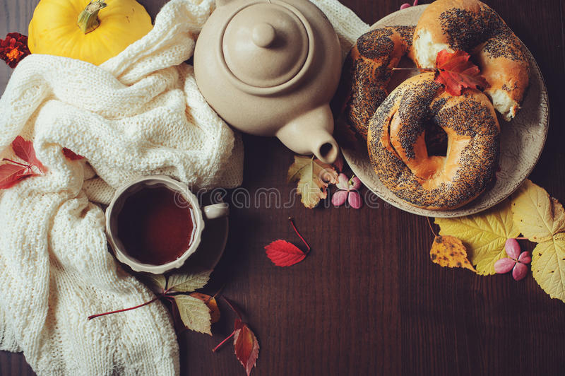 Flat lay of cozy autumn breakfast on table in country house. Hot tea, pumpkins, bagels and flowers. stock photo