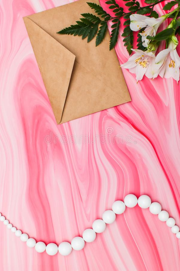 Flat lay with craft envelope with white flowers and beads on pink marble texture table royalty free stock images