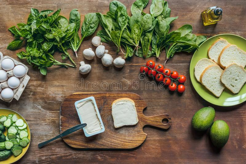 flat lay with cream cheese and piece of bread on cutting board and various ingredients for cooking breakfast stock images