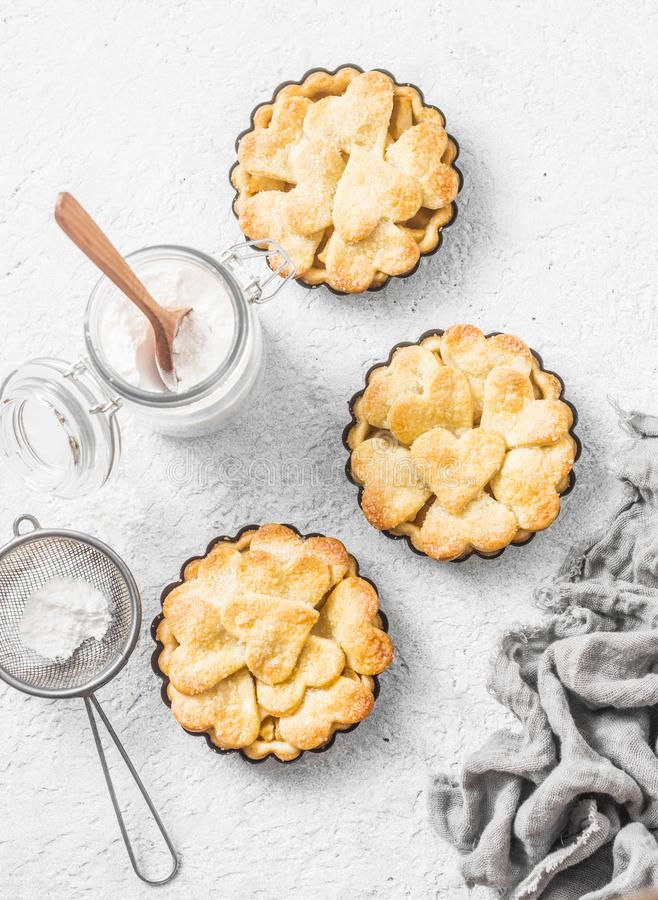 Flat lay crispy shortcrust pastry apple tartlets in the baking dish on light background, top view. Valentine`s day baking stock image