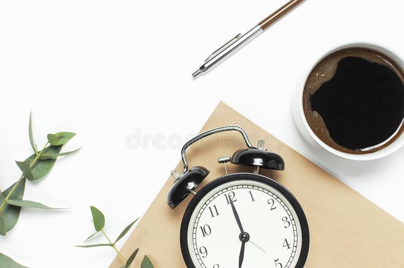 Flat lay cup of black coffee, black alarm clock, notebook, diary, eucalyptus on white background top view copy space. Minimalistic. Food concept, Feminine desk stock photography