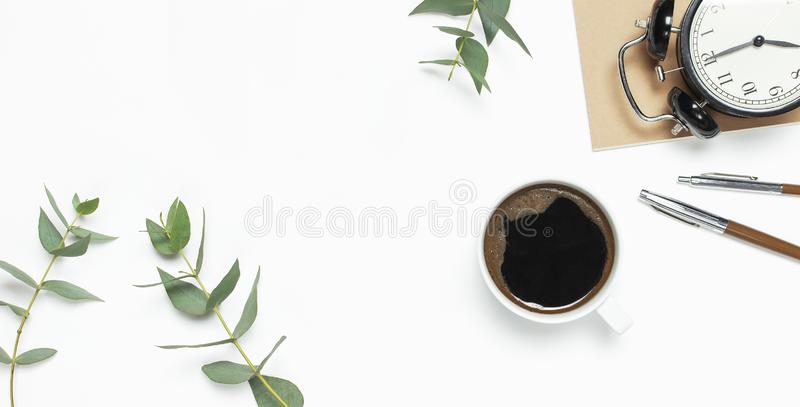 Flat lay cup of black coffee, black alarm clock, notebook, diary, eucalyptus on white background top view copy space. Minimalistic. Food concept, Feminine desk stock images