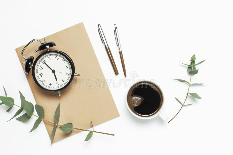 Flat lay cup of black coffee, black alarm clock, notebook, diary, eucalyptus on white background top view copy space. Minimalistic. Food concept, Feminine desk stock image