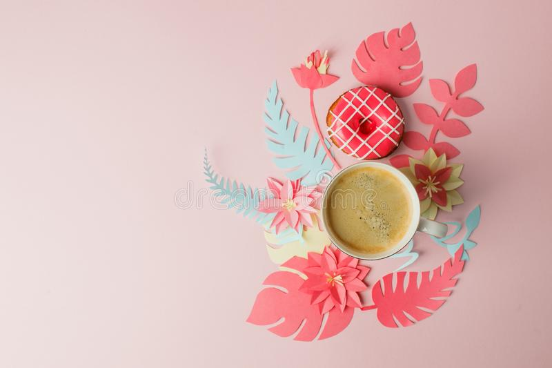 Flat lay with cup of coffee and pink donut, modern origami papercraft flowers copy space. Woman day, 8 March. pink background. royalty free stock images